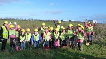 Schoolchildren in yellow hard hats standing in a field