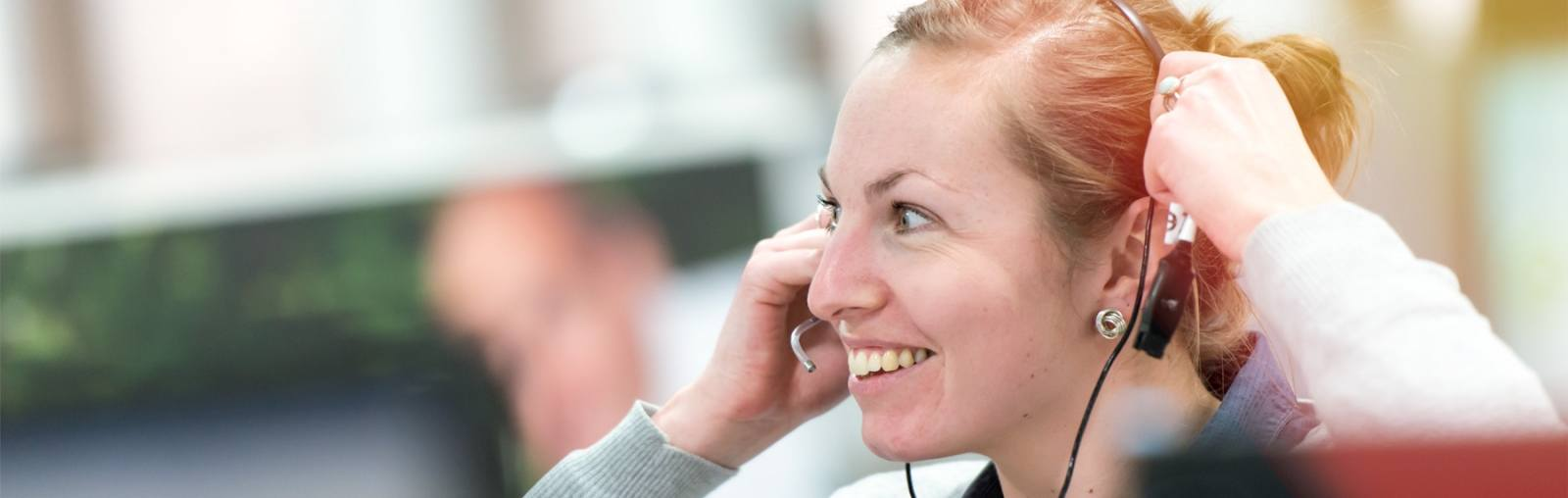 Lady smiling wearing a telephone headset