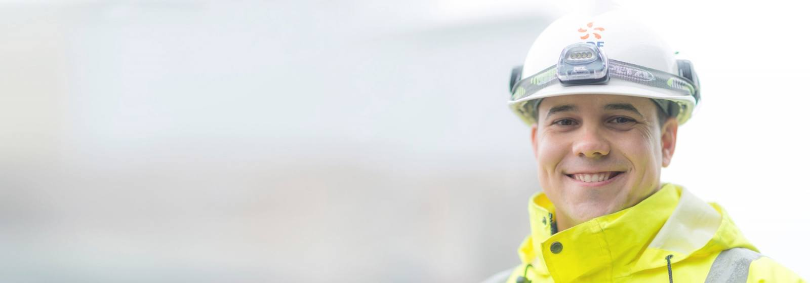 Picture of an engineer in a white hard hat smiling