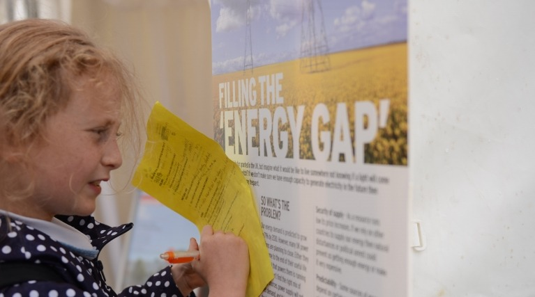 Picture of a young girl making notes from an EDF Energy information poster at at a science festival