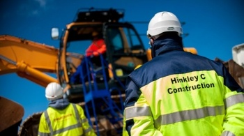 Construction workers standing by a mechanical digger