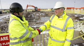 Two workers shaking hands on a construction site